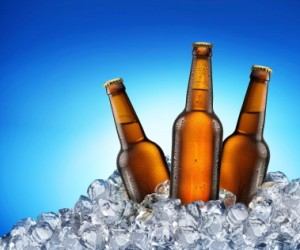 Three beer bottles getting cool in ice cubes. Isolated on a blue.