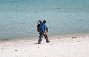 girl backpacker walking on a beach