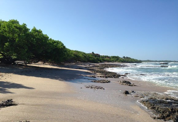 Playa Langosta is a residential area where the trees line the sand, offering plenty of shade. And the surf crashing against the rocks provides a dramatic backdrop.